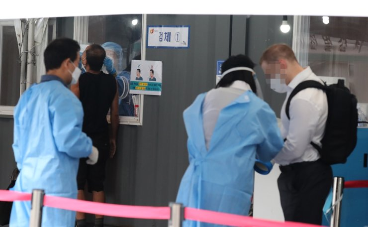 Medical workers guide a person at a temporary COVID-19 testing center in front of Seoul Station, Wednesday. Yonhap