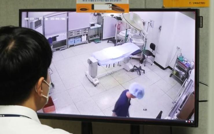 An employee at a hospital in Dobong District, northern Seoul, looks at the monitor showing the inside of an operating room through a surveillance camera, Aug. 23. Yonhap