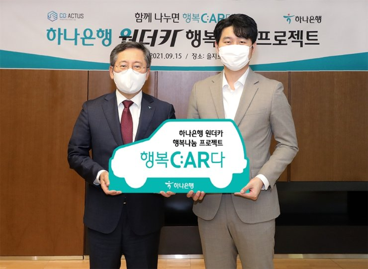 Hana Bank CEO Park Sung-ho, left, poses with CO:ACTUS CEO Song Min-pyo after donating two vehicles for the startup that operates a mobility service, at the former's headquarters in Seoul, Wednesday. Courtesy of Hana Bank