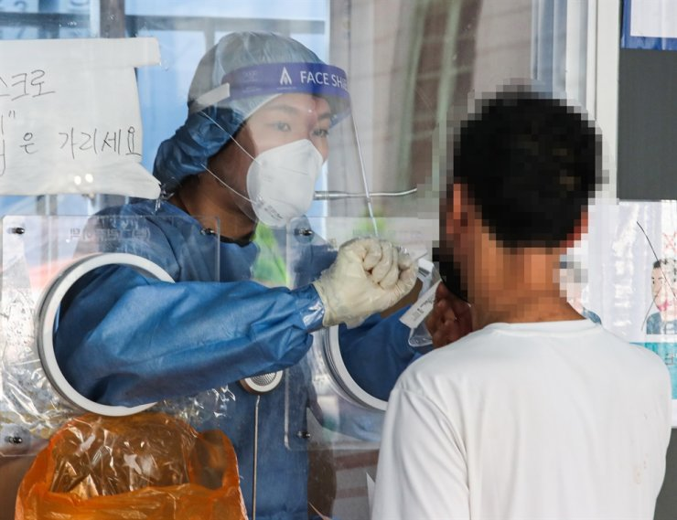 An individual gets tested for the coronavirus at a testing center near Seoul Station, Friday. Yonhap