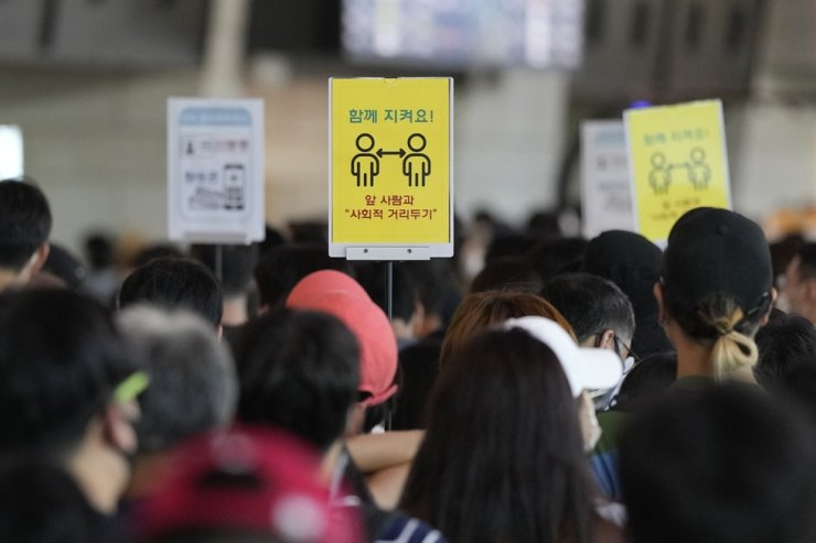 Signs promoting social distancing are seen as passengers wait to board planes ahead of the Chuseok holiday, which falls on Sept. 21, at the domestic flight terminal of Gimpo airport in Seoul, Sept. 18. AP-Yonhap