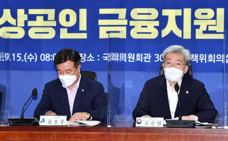 Financial Services Commission Chairman Koh Seung-beom, right, speaks during a government-ruling party meeting at the National Assembly in Seoul, Wednesday. Yonhap