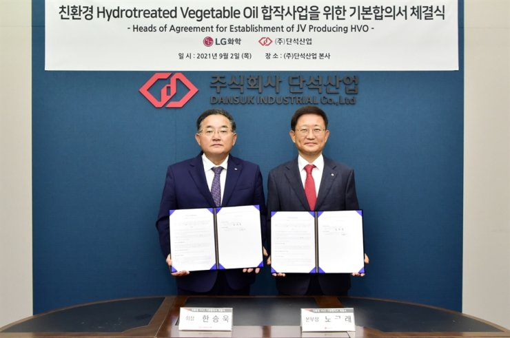 Noh Kug-lae, left, head of petrochemical business at LG Chem, poses with Dansuk Industrial Chairman Han Seung-uk at the latter's headquarters in Siheung, Gyeonggi Province, Thursday, after signing a contract to build a hydrotreated vegetable oil manufacturing facility. Courtesy of LG Chem