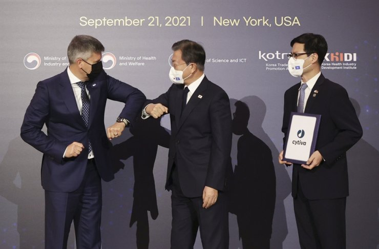 President Moon Jae-in bumps elbows with Cytiva CEO Emmanuel Ligner, left, who submitted a $52.5-million investment plan to Korea, during a signing ceremony for a South Korea-U.S. global vaccine partnership in New York, Tuesday. On the right is Korea's Trade Minister Yeo Han-koo. Yonhap