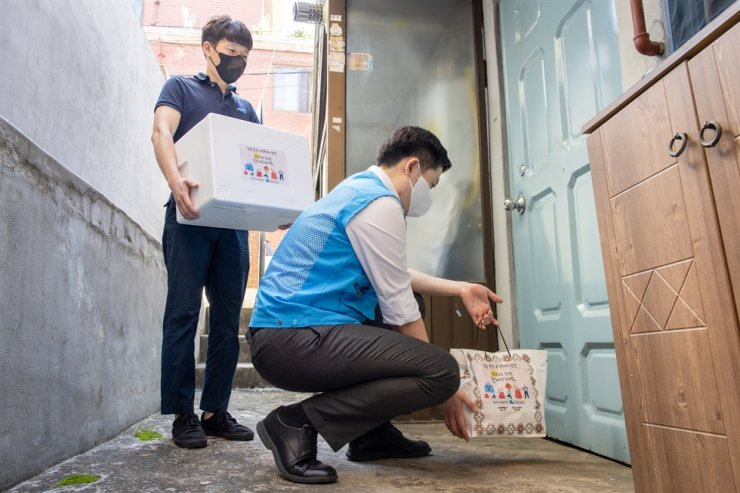 Officials from a social welfare center in Yeongdeungpo District in Seoul deliver meal boxes to the house of a senior citizen living alone, Wednesday. Courtesy of Eximbank