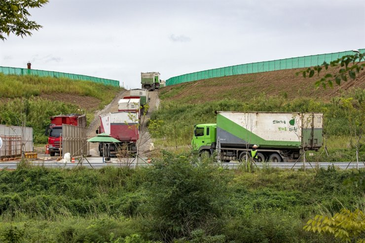 Trucks carrying waste head to a landfill in Incheon's Seo District, Sept. 1. Korea Times photo by Shim Hyun-chul