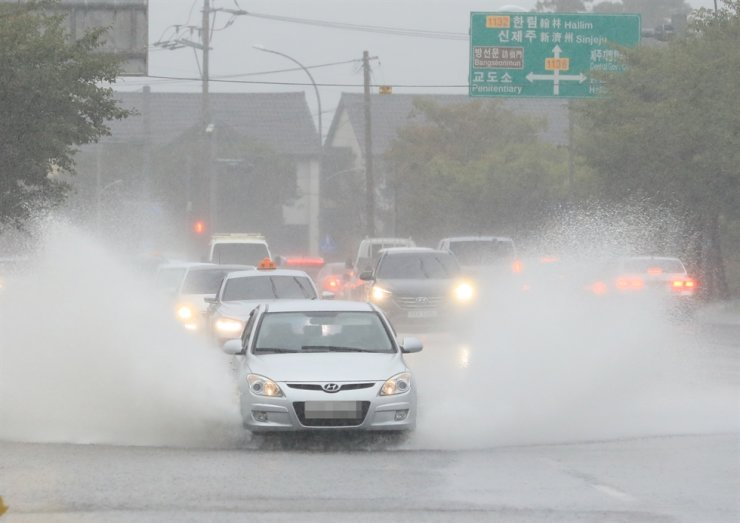 Cars drive through rain on a flooded road on Jeju, Sept. 14. Yonhap