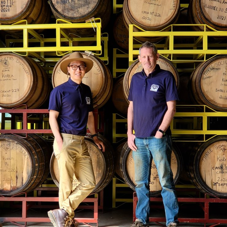 The founder and CEO Bryan Do, left, and master distiller Andrew Shand, stand in front of casks at the Three Societies distillery in Namyangju, Gyeonggi Province. Courtesy of Three Societies