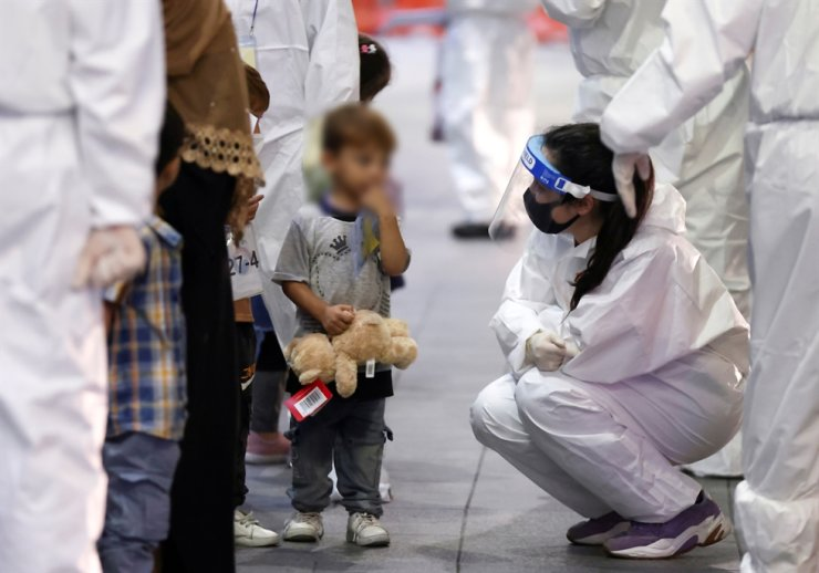 A boy receives attention from an official as Afghan evacuees who supported the Korean government's activities in Afghanistan arrive at Incheon International Airport in Incheon, Aug. 26. Reuters-Yonhap