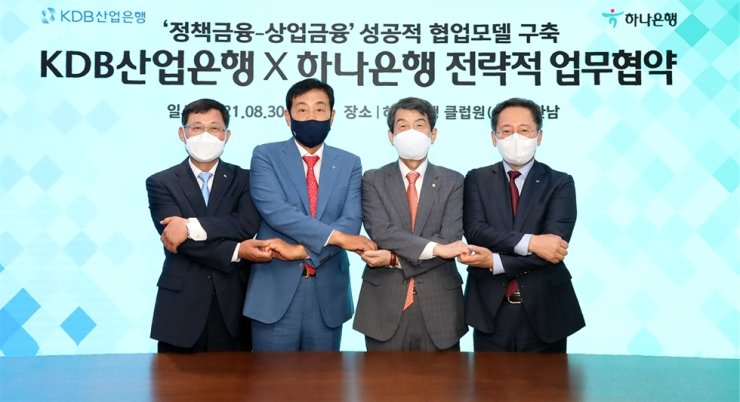 Korea Development Bank CEO Lee Dong-gull, second from right, Hana Financial Group Chairman Kim Jung-tai, second from left, and Hana Bank CEO Park Sung-ho, right, join hands after signing a strategic partnership, Aug. 30. Courtesy of Hana Bank