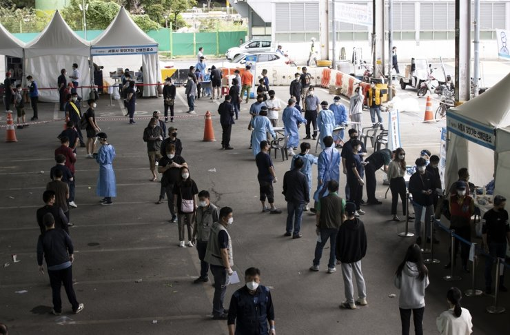 Merchants and residents wait in long lines for COVID-19 testing at Garak Market in Seoul's Songpa District, Monday, as the market has reported a high number of COVID-19 infections. Yonhap