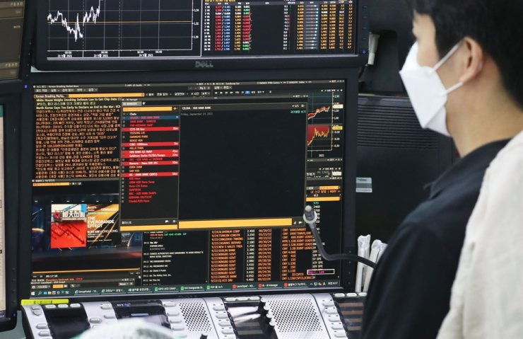 A trader reads news about the Evergrande situation on a computer in a dealing room of a branch of Hana Bank in Seoul, Friday. Yonhap