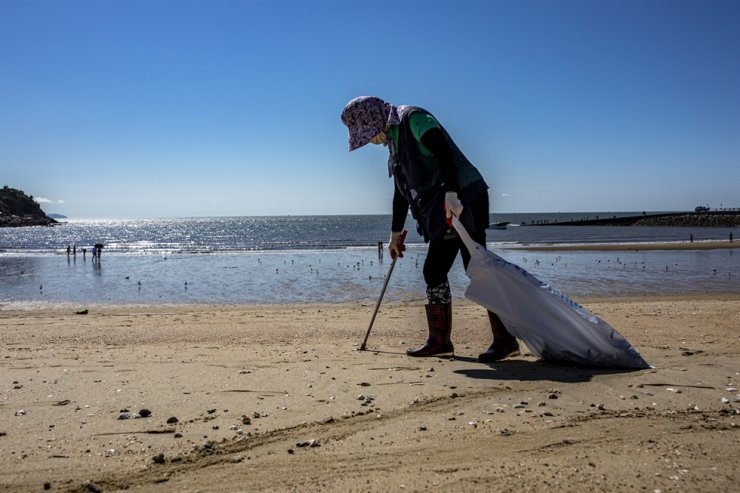 An official from Incheon's Jung District collects waste from Eurwangni Beach, Sept. 8. Korea Times photo by Shim Hyun-chul