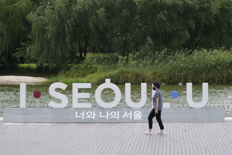 A visitor wearing a face mask to help curb the spread of the coronavirus walks near the display of the Seoul logo during a lunch break at a park in Seoul, Sept. 6. AP-Yonhap