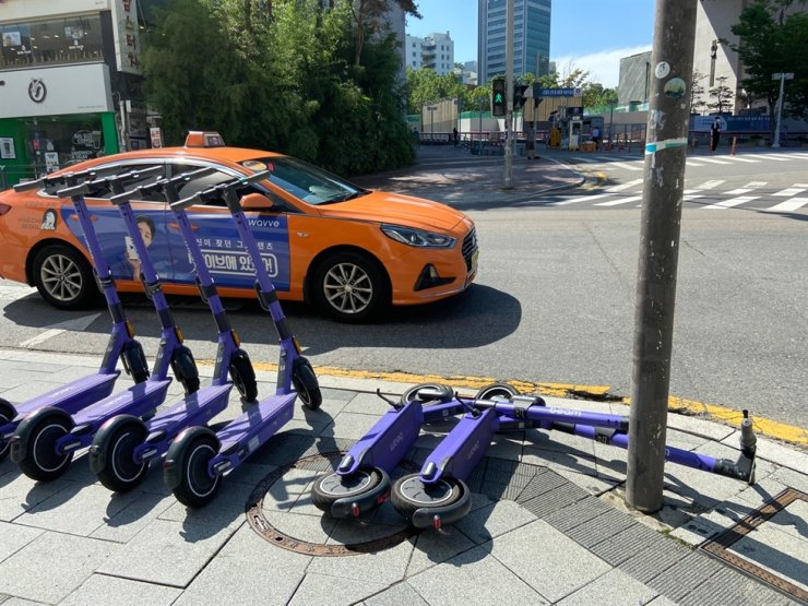 In this July 21 file photo, electric scooters are parked near Hongik University in Seoul. Korea Times file