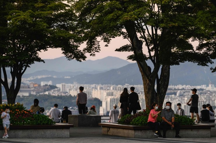 Visitors stand on an observation deck beneath the Seoul Tower with a view of residential and commercial buildings in Seoul, Sept. 3. AFP-Yonhap
