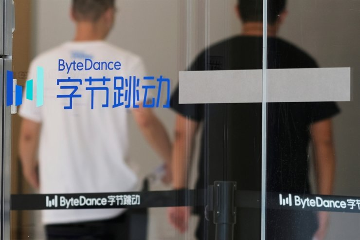 People walk past a logo of Bytedance, the China-based company which owns the short video app TikTok, or Douyin, at its office in Beijing, July 7, 2020. Reuters-Yonhap