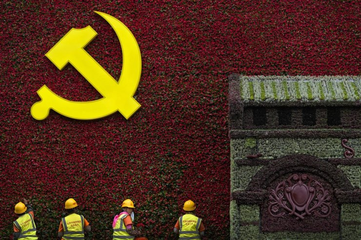 In this June 16 file photo, workers install flowers on a decoration with a Communist Party's logo in Beijing. AP-Yonhap