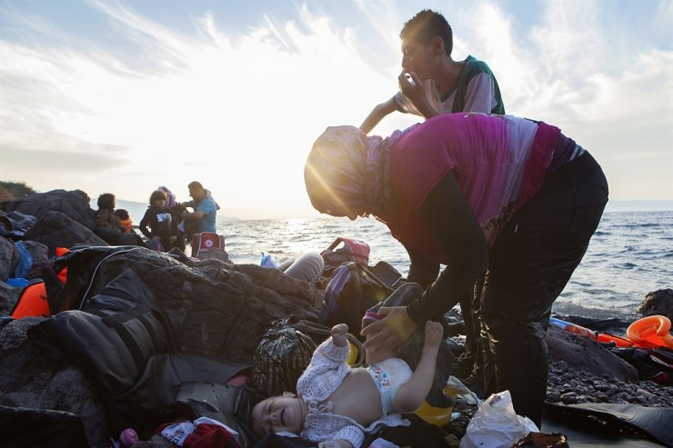 A Syrian woman changes her baby's diaper shortly after touching down on the shore of Lesbos ― an island of Greece ― in a photo taken in September 2015. Courtesy of Harry Chun