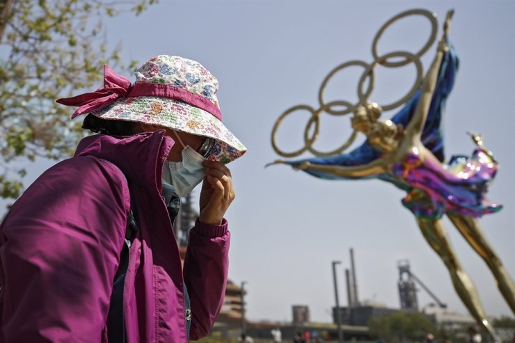 In this May 2 file photo, a woman adjusts her face mask as she walks by a statue featuring the Beijing Winter Olympics figure skating on display at the Shougang Park in Beijing. AP-Yonhap