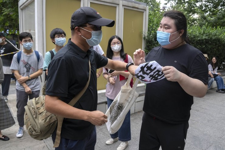 A man pulls a sign reading 'stand together' away from a supporter of Zhou Xiaoxuan outside a courthouse in Beijing, Sept. 14. AP-Yonhap
