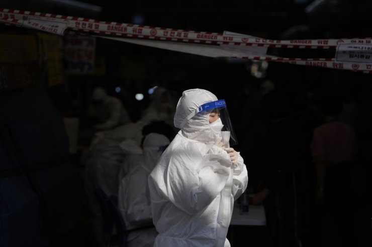 A health officer wearing protective gear directs visitors waiting in line to get a COVID-19 test at a temporary screening clinic in Seoul, Sept. 24. AP-Yonhap