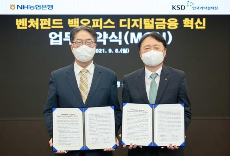NongHyup Bank CEO Kwon Jun-hak, right, and Korea Securities Depository Rhee Myong-ho pose at the bank's main branch in Seoul, Monday, after signing a memorandum of understanding to help venture capital firms digitize their back offices. They agreed to open their digital platforms for this goal in October. Courtesy of NongHyup Bank