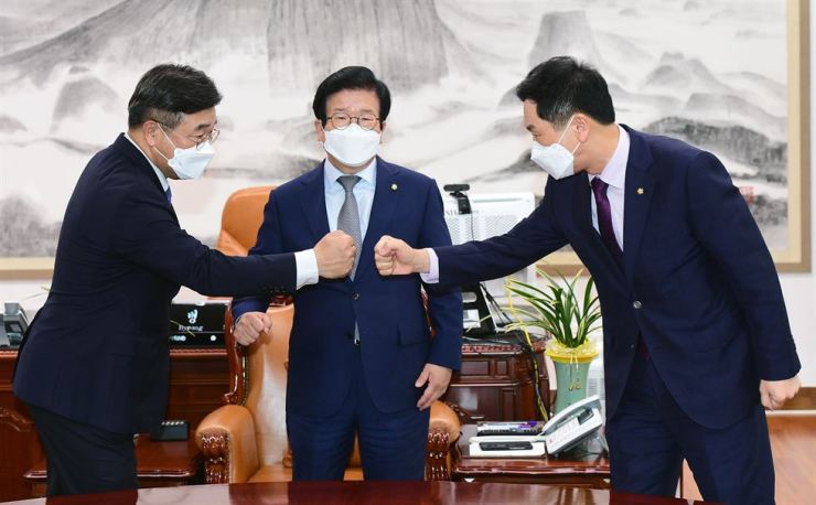 Floor leaders of the two major parties, Rep. Yun Ho-jung of the ruling Democratic Party of Korea, left, and Rep. Kim Gi-hyeon of the main opposition People Power Party, right, fist-bump each other during a meeting presided over by National Assembly Speaker Park Byeong-seug in his office at the Assembly, Wednesday, to discuss the contentious 'fake news' bill. They decided to form a special committee for further discussion on the matter through Dec. 31. Yonhap