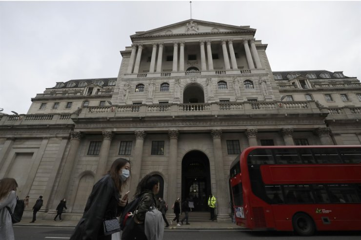 Pedestrians wearing face masks walk past the Bank of England in London in this file photo taken on March 11, 2020. The U.K. posted the biggest jump in annual inflation on record last month as global supply shortages and rising wages magnified the scale of price increases after pandemic-related discounts a year ago. AP-Yonhap