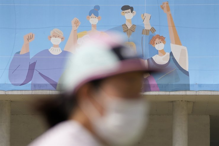 A woman wearing a face mask runs near a banner for COVID-19 vaccination in Seoul, Sept. 10. AP-Yonhap