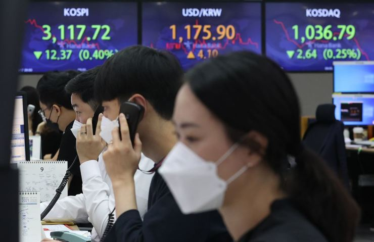 Dealers at Hana Bank work in a trading room at its headquarters in Seoul, Friday. Yonhap
