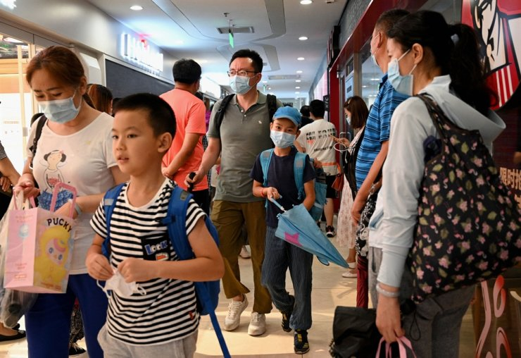 Students and parents walk after attending a private after-school education class in the Haidan District of Beijing, in this July 29 photo. AFP-Yonhap