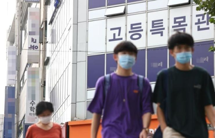 People pass a building housing the offices of private academies in Seoul in this Aug. 28, 2020 photo. Yonhap