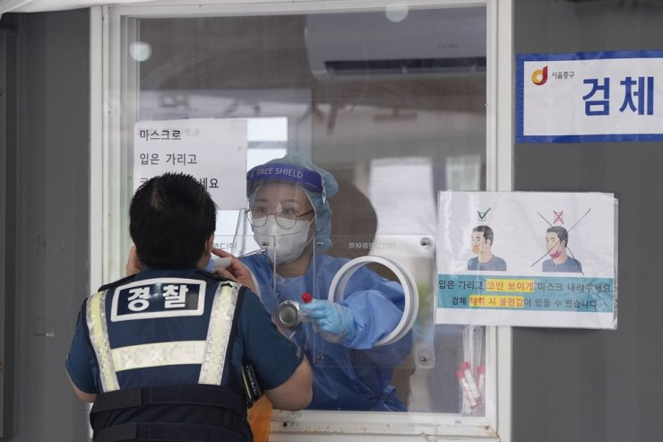 A medical worker in a booth takes a nasal sample from a police officer during coronavirus testing at a makeshift testing site in Seoul, Sept. 25. AP-Yonhap