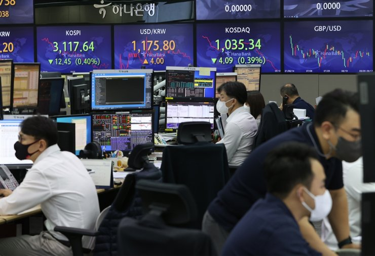 Traders are seen at the Hana Bank's dealing room in Seoul, Friday. Yonhap