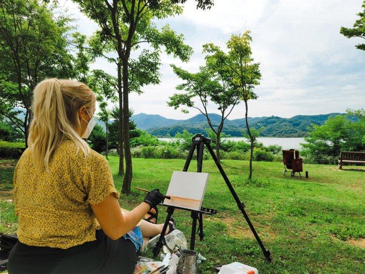Tahni Osterman paints a landscape 'en plein air.' / Courtesy of Otahni Studio