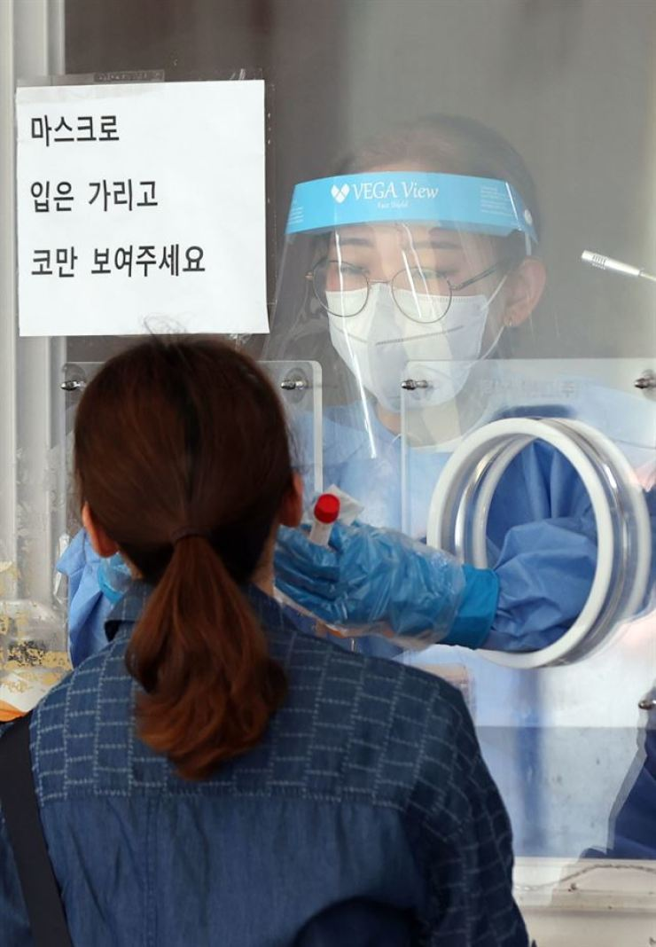 A woman gets tested for COVID-19 at a temporary center in Seoul Station, Sept. 10. Yonhap