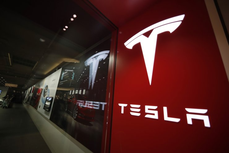 This file photo shows a sign with Tesla's logo outside a Tesla dealership in the United States. AP-Yonhap