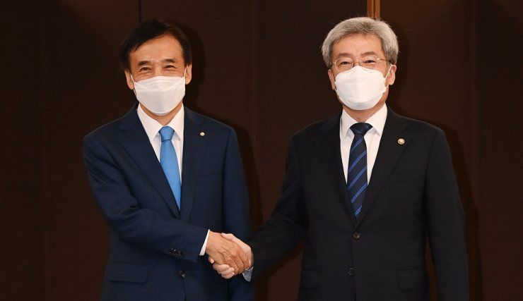 Financial Services Commission Chairman Koh Seung-beom, right, shakes hands with Bank of Korea Governor Lee Ju-yeol at the central bank's headquarters in Seoul, Friday. Yonhap