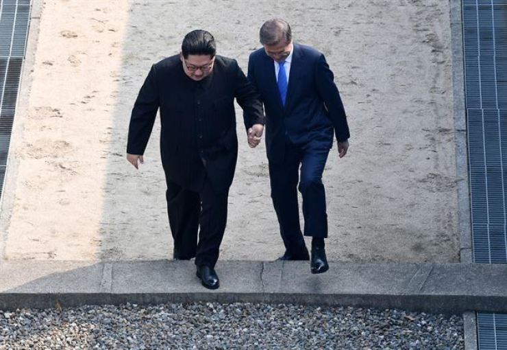 President Moon Jae-in and North Korean leader Kim Jong-un hold hands as they cross the military demarcation line during their first meeting at Panmunjeom, April 27, 2018. Korea Times file