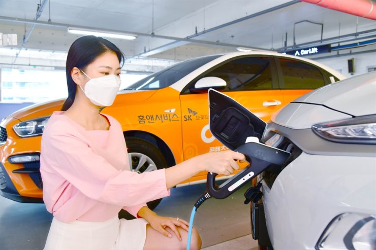 A woman charges her car with Home & Service's electric charger in an apartment complex garage in Seoul on Sept. 8. Courtesy of SK Broadband