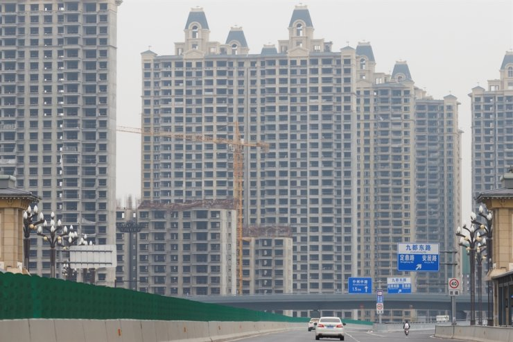 Vehicles drive near unfinished residential buildings at the Evergrande Oasis, a housing complex developed by Evergrande Group, in Luoyang, China, Sept. 16. Reuters-Yonhap