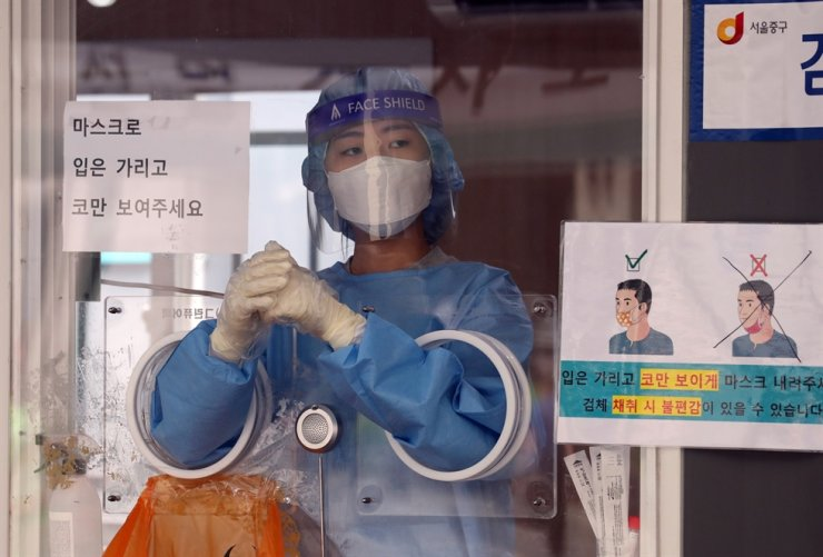 A medical worker waits for the next person to get tested for COVID-19 at a testing center in Seoul Station, Sept. 12. Yonhap