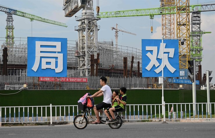 People commute in front of the under-construction Guangzhou Evergrande football stadium in Guangzhou, China's southern Guangdong Province, Sept. 17. AFP-Yonhap