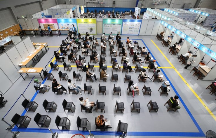 People wait to receive coronavirus inoculations at a vaccination center in Mapo District, Seoul, Tuesday. As of that day, 60.1 percent of the population have received at least their first shot of a vaccine. The government is targeting a 70 percent first-shot vaccination rate before the Chuseok long weekend, which falls from Sept. 18 to 22. Yonhap