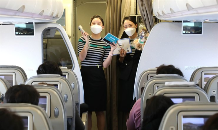 Flight attendants of Air Seoul carry out an event for passengers who boarded the airline's 'international sightseeing flight' on Feb. 21. Joint press corps
