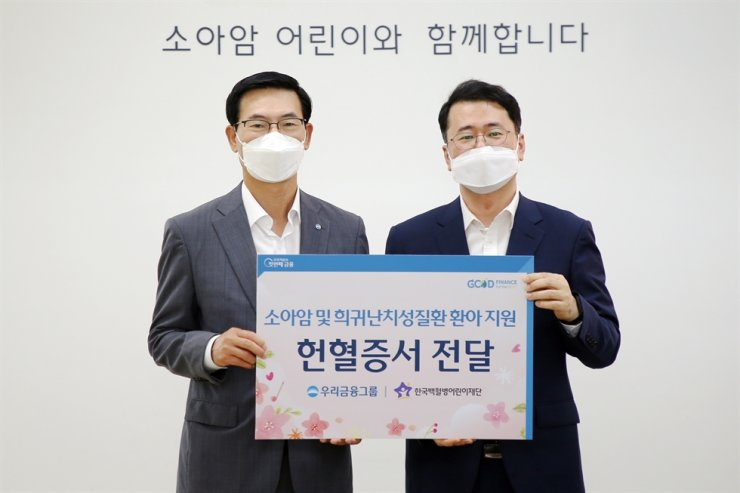 Woori Financial Group Vice President Choi Dong-soo, left, poses with Korea Childhood Leukemia Foundation Secretary General Seo Sun-won after presenting blood donation cards from the group's employees, at the foundation's headquarters in northern Seoul, Wednesday. Courtesy of Woori Financial Group