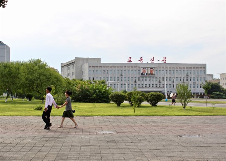 A young couple hold hands as they pass the Rodong Sinmun building, home to the official newspaper of the Workers' Party of Korea, in this August 2018 photo. Courtesy of Lindsey Miller