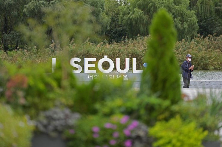 A visitor wearing a face mask to help curb the spread of the coronavirus walks near the display of the Seoul logo in Seoul, Oct. 6. AP-Yonhap