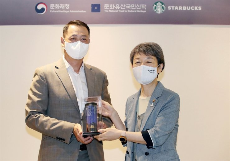 Starbucks Korea CEO Song Ho-seob receives a commemorative tumbler from the Culture Heritage Administration's former administrator Chung Jae-suk during a heritage reserve sponsor ceremony in Seoul, June 17, 2020. Yonhap
